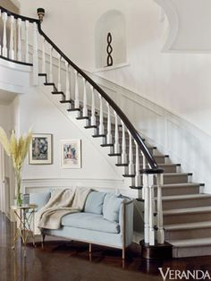 white staircase with a blue sofa underneath it- courtesy of JLO