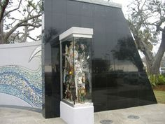 The Katrina Memorial in Biloxi, Mississippi is located near Highway 90 in Biloxi's Town Green. It is dedicated to the Gulf Coast victims who perished in Hurricane Katrina.  The memorial contains a tile inlay of a wave, and a glass case containing various items from destroyed homes and buildings.