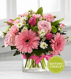 """FTD® proudly presents the Better Homes and Gardens® Blooming Vision™ Bouquet. Offer them a bouquet blooming with a """"fresh from the garden"""" appeal. Pink roses, hot pink tulips, pink mini carnations and pink gerbera daisies are accented with white Monte Casino asters and lush greens. Gorgeously arranged in a clear glass cube vase accented with a pink satin ribbon, this bouquet is a soft and graceful way to send your warmest sentiments."""