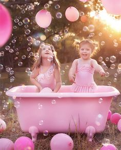 A pink tub, pink balloons, and bubbles everywhere!
