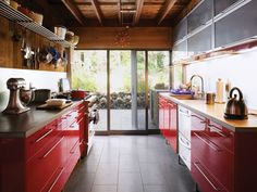 The kitchen of a 1967 home in Amagansett, New York, was given a modern makeover with simple Ikea components, new appliances and fixtures, and warm finishes, such as red lacquer and cypress woodwork.