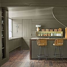 Plank the Room | Olive-gray wood panels run over the walls and ceiling of this kitchen. Even the refrigerator is hidden behind paneling for a seamless transition from the living room. | SouthernLiving.com