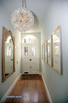 Long narrowhallway decorating ideas - love the the feature lampshade and the mirror maximising light
