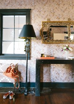 A bronze floor lamp and black console ground the botanical wallpaper in the entry. Interior design by Chloe Warner; Lonny September 2014.