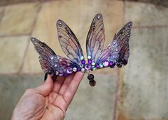 A beautiful tiara, fit for any fairy bride! The delicate fairy wings are attached a metal silver band, and adorned with clear, purple and pink coloured gems and beads. This tiara is light weight, sturdy and one size should fit all. Due to its small and fragile parts, I would say it
