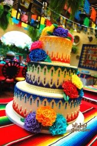 Dia de los muertos cake? Not sure about getting married with this theme but I am loving the bright colors of this cake and bright colors of the wedding.