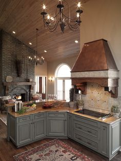 The brick fireplace, wood floors, vaulted ceiling, gray cabinets, and lighting