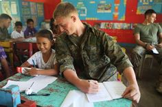 """""""Marine pretending to cheat off a 4th graders math exam. - Philippines"""" This is so adorable"""