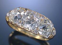 DIAMOND RING, LATE 19TH CENTURY The three circular-cut diamonds embellished with rose-cut diamond highlights