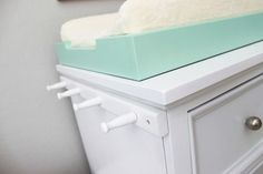 So smart! Attach a peg rail to the side of your changing table/dresser for added storage. #nursery #organization