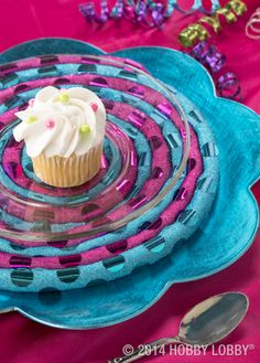 For an on trend place setting that echoes our sugary theme, we dreamed up a lovely lollipop charger. To make it, wrap two hues of polka-dot ribbon around equal lengths of piping filler cord. Then swirl them together into a spiral as shown, securing with hot glue as you work.