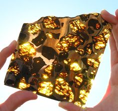 """Pallasite meteorite.  This stony-iron meteorite is often called """"celestial stained glass"""", and from this photo it is easy to see why.  One of the most beautiful things in the Solar System."""