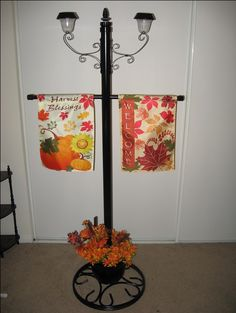 Dual Solar Lamp Post and Garden Flag display for Glamping, your Garden or Patio. Made from inexpensive Solar Stake lights, Metal Plant hanging brackets, PVC pipe, dollar store flower pot and an old umbrella stand!