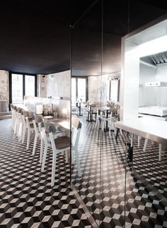 Black and white cement tiles inspired by Parisian hallways cover the floors. Parisian hamburger restaurant by French studio Cut Architectures.