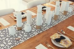 Graphic dinner party table setting: triangles, dots, gold, white, black.