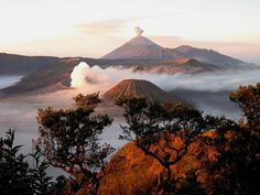 Mount Bromo, with Mount Semeru erupting in the background.