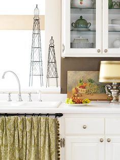 Cook's Delight. In the kitchen, white cabinets pop off the room's chocolate wall color. The wire obelisks, the urn lamp, and the vintage painting add visual interest. Glass-front cabinets above the counter create an open feel without sacrificing storage.
