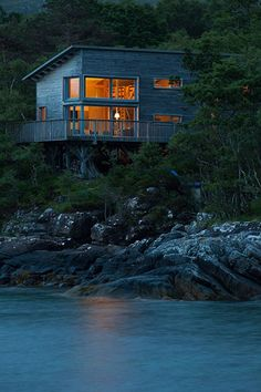 Homes - On The Rocks: wooden house by sea at night