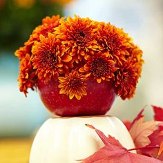 For quick, fun decor, combine two fall favorites: mums and apples. Use a nail, awl, or even a drill with a 1/4-inch bit to make holes in the top of each apple about 1-1/2 inches deep. Snip off mum blooms with 2-inch stems and insert them into the holes. These are best made the day of your party to keep them looking fresh.