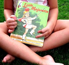 It wasn't too long ago when every little girl in America spent their days practicing twirling a baton.     This book, Little Majorette, by Dorothy Grider is a classic piece of Americana. This color illustrated book has a distinctive mid-century feel as it follows Patty on her quest to become a majorette.