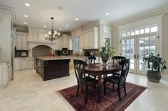 Luxury home with open living space with kitchen opening to dining area.  Kitchen features white cabinets and dark wood island