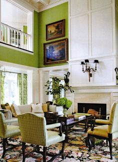 Two story family room, I like the paneling above and around fireplace and sheet rock on top. Great ideas on how to make a two story room feel warmer.  (Green paint and furniture not really my style)
