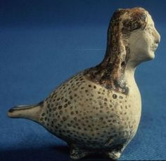 Aryballos in the shape of a siren. Corinthian. ca. 580 BC - ca. 570 BC, Museum of Fine Arts, Boston. The vase is modelled in the shape of a siren. Brown spots of paint cover the body, and the tail, feet, and hair are also painted brown. There is red overpainting in the hair. There is a hole at each side of the neck for suspension, and a hole for filling at the top of the head. Perseus:image:1990.24.0313