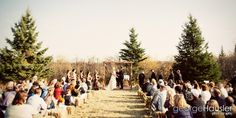 Country Wedding: Ceremony out in a field with everyone watching while sitting on hay bales.