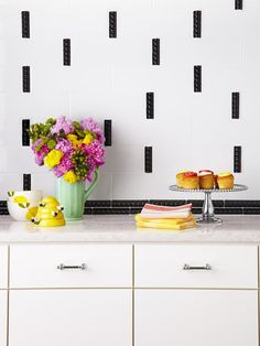 Large white subway tiles were mixed with skinny black accent tiles to create this awesome #kitchen backsplash