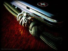 Two-strand footrope knot paracord pocket knife fob with Kiko Tiki pewter lanyard bead from Schmuckatelli Co.