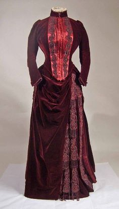 Dress, ca. 1880-90, dark wine-coloured velvet. Long-waisted bodice laced down front with high collar and red satin facing. Skirt has large bustle and pleats at side, both heavily decorated with red glass beads and bugles.