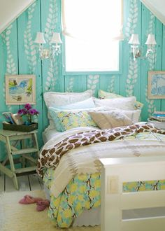You don't need a headboard when you have a pretty pattern on the wall behind the bed. A simple stencil pattern sprouts up the wall of this bedroom and turns it into a focal point. Cheerful spring designs on the bed make the space a welcome spot for afternoon naps and lingering mornings.