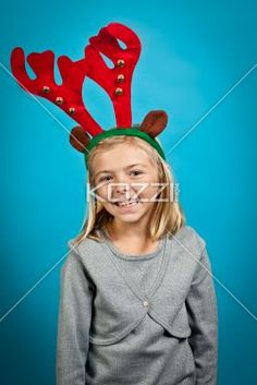 girl wearing reindeer antlers - Shot of a little girl smiling and wearing reindeer antlers, isolated on blue. Model: Alyssa Powers