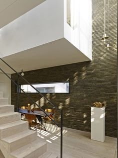 Walls of dark brick connect the exterior and interior of this mews house in the north London borough of Hackney