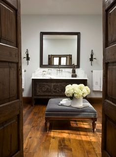 Spanish style master bathroom with gray walls paint color, blue velvet tufted ottoman with nailhead trim, Spanish cabinet vanity with marble countertop and rustic wood floors