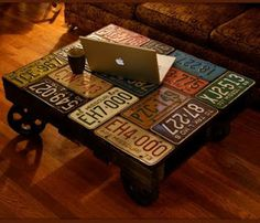 """License plate pallet coffee table.  This post is especially for """"car lovers"""" on duty!  It is a base table decorated plates of automobiles. This model is quite rustic, made a pallet on which were placed large metal wheels.  One idea that I can add is that you can put a glass over the plates, the surface is more homogeneous."""