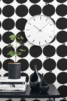 black polka dots, which background, large clock, plant, black table, black vases