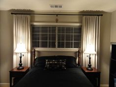 bed under - w/blinds and curtains. All that would be needed was more color, a head board and more pillows and maybe a valance!!