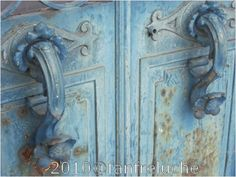 Old blue handles on crypt's wrought iron door. In Paris.