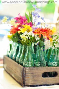 vintage bottles, flowers in coke bottles, wedding flowers, flower vases, bottles with flowers, retro centerpiece, wooden crates, wedding centerpieces, coke bottle flowers