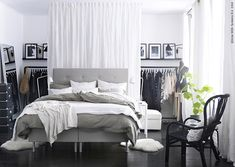 No closet solution: ceiling to floor drapes to hide one whole end of the room which has been fitted with clothes rods, shelf, etc.