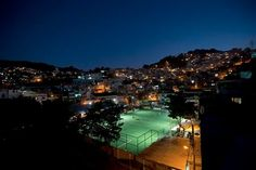 Image: Residents of the Morro da Mineira favela play in the newly installed soccer pitch powered by player's footsteps, in Rio de Janeiro, Brazil. The project, sponsored by British oil giant Shell, has around 200 energy-capturing tiles installed along the width and breadth of the field and covered by a layer of AstroTurf. Working in conjunction with solar panels also installed around the field, the player-powered tiles feed electricity to a system of floodlights overhead.