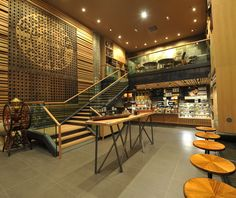 Located at the Carrousel du Louvre in Paris, this store features wood siding made from champagne boxes recovered from French winemakers, chairs and coffee tables designed by local craftsmen, and repurposed coffee grinders purchased from neighboring flea markets. starbuck, pari