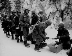"During the Battle of the Bulge, this GIs from ""Item"" Company, 347th Infantry Regiment, 87th Infantry Division, await their turn in line to be served with food near the city of Saint-Hubert, province of Luxembourg, Belgium. 13 January 1945. by World War 2 Photos, via Flickr"