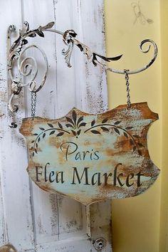 Paris flea market advertising sign hanging from an ornate bracket