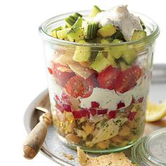 Picnic in a Glass~ This Southern spin on Middle Eastern fattoush salad can be assembled in the morning before taking off to your picnic, tailgate, or work so the flavors meld and pita chips soften. Serve it directly from the jars.  /   SouthernLiving.com