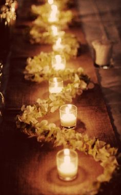 White and green (orchids maybe) leis down the rest of the table. With mercury candle holders in between.