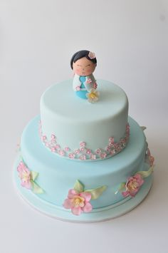 Blue cake with pink flowers and doll topper