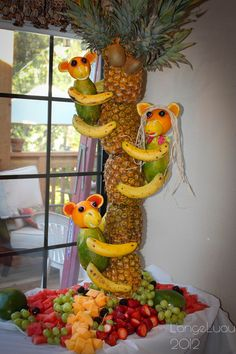 I made this for our annual luau party - it turned out so cute!   I used pineapples for the tree, oranges for the heads, lemons for the noses, radishes & black grapes for the eyes, papya's for the bodies and bananas for the arms & legs. My husband made a thin, sturdy, metal  pole on a stand that we skewered the pineapples on, then we attached the monkeys with bamboo skewers that we cut to legnth.   It took us about 1 hour to create this from start to finish. You can do it too! It was a huge hit!