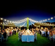 Guests dine in the garden under bright string lights as the sun sets along the horizon.